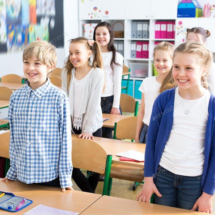 Kinder stehen bei der Schule Bänke