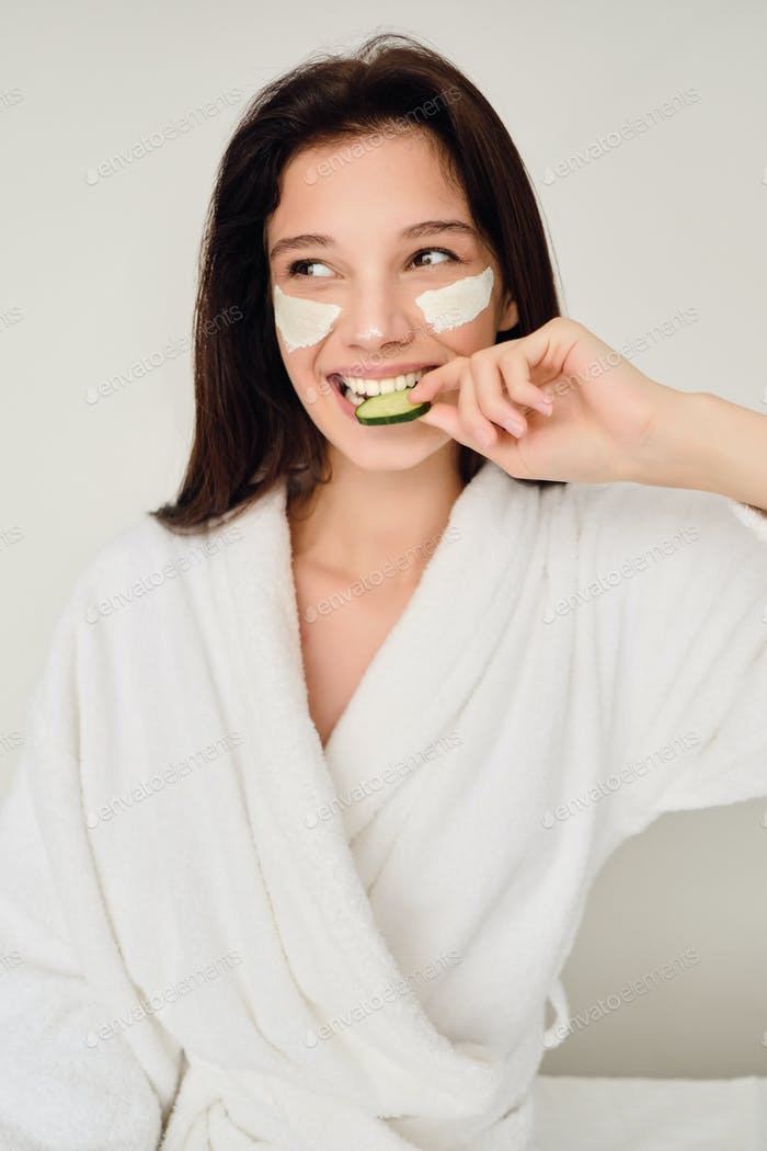 Smiling woman in bathrobe with cosmetic mask on face sitting on bed eating slice of cucumber