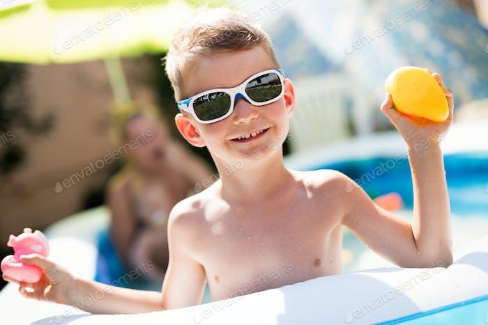 Happy boy enjoying summer time in swimming pool
