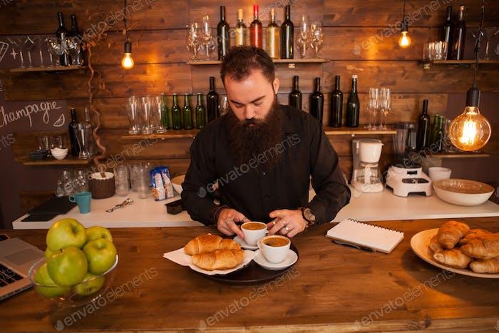 Beaded hipste waiter preparing cofffe behind the bar