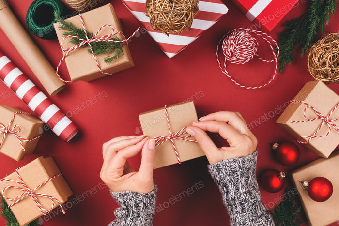 Wrapping Process. Cristmas Giftson Red Background.