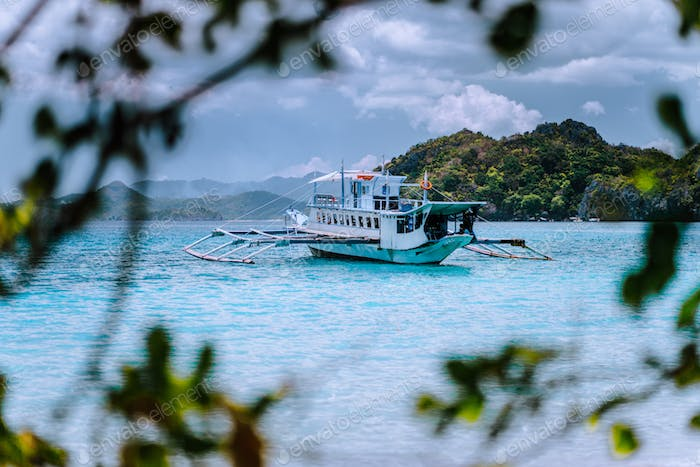 Tourism divers boat in blue cadlao lagoon framed by leaves. Island hopping tour, El Nido, Palawan