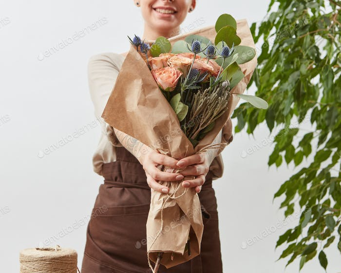 Smiling girl florist with beautiful bouquet in her hands on a light background with green leaves