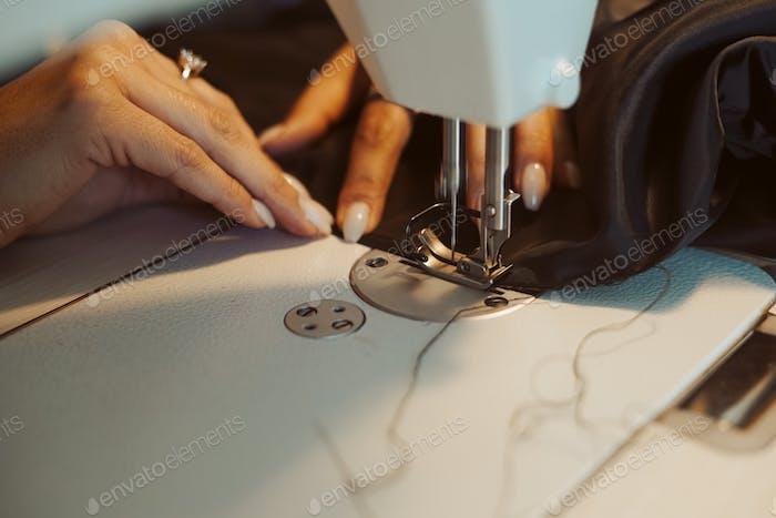 Frau Schneider Hände arbeiten an Nähmaschine.
