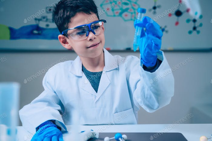 Junge im Labor Mantel hält Reagenzglas
