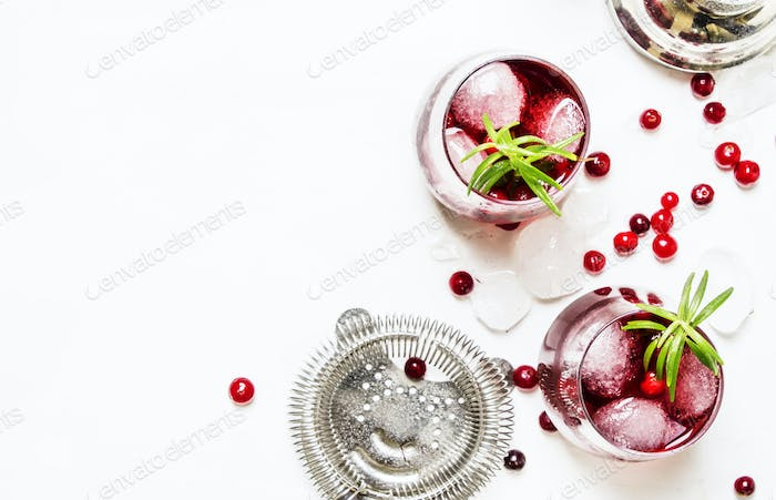 Cranberry cocktail with ice, rosemary and berries