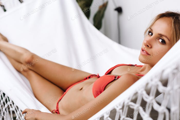 Woman laying down and relaxing on white hammock