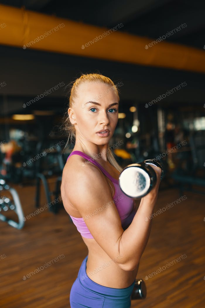 Young woman in pink top and mini shorts doing exercise with dumbbells while training arms at the gym