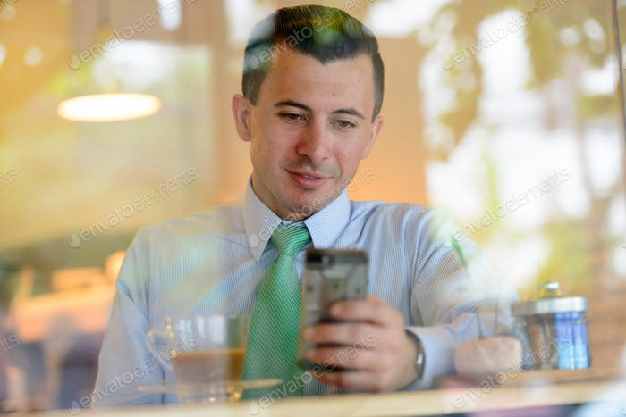 Young businessman using phone at the coffee shop