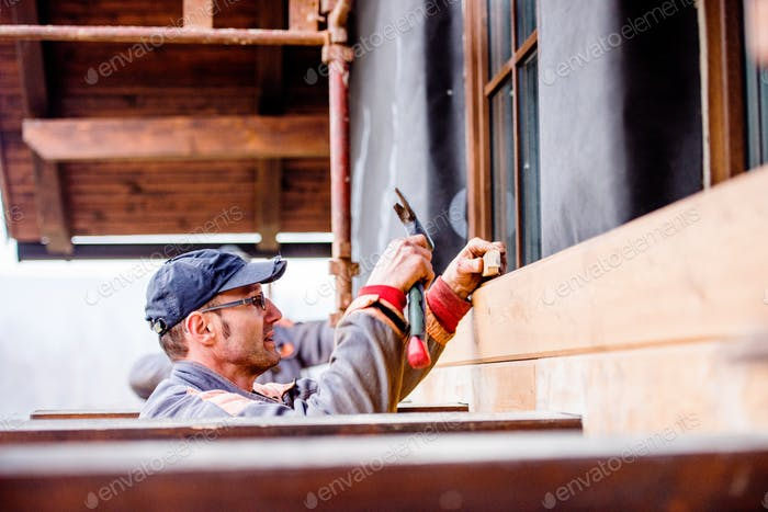 Construction worker thermally insulating house, doing wooden fac
