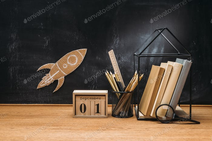 close up view of cardboard rocket on blackboard, calendar, magnifying glass and books on wooden