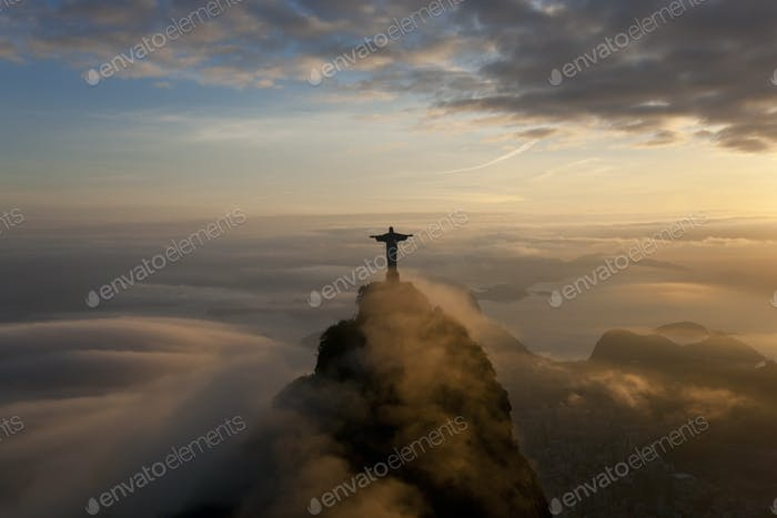 High angle view of colossal Christ Redeemer statue surrounded by clouds at dusk, Corcovado, Rio de