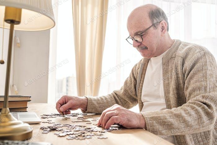 Senior caucasian man working on a puzzle