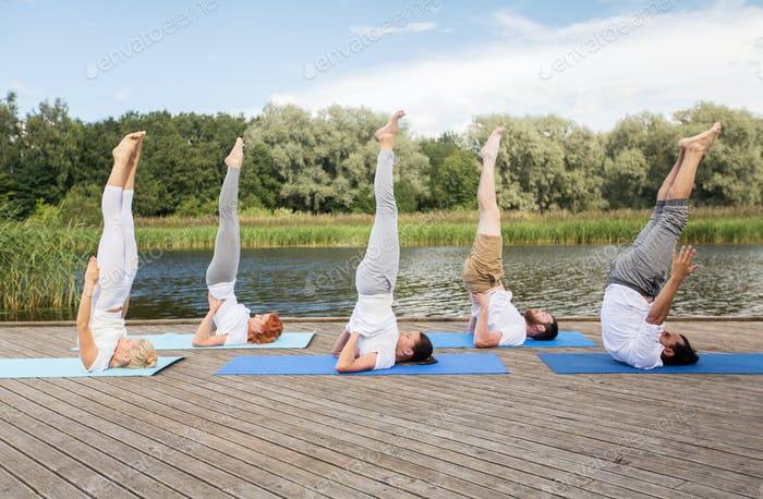 people making yoga in shoulderstand pose on mat