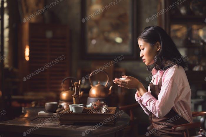 Junge Frau gießt Tee