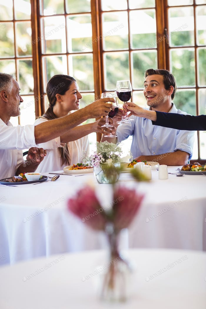 Happy business people toasting wine glasses in restaurant