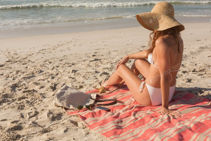 Side view of gorgeous young Caucasian woman in hat and bikini relaxing on beach. It is sunny day