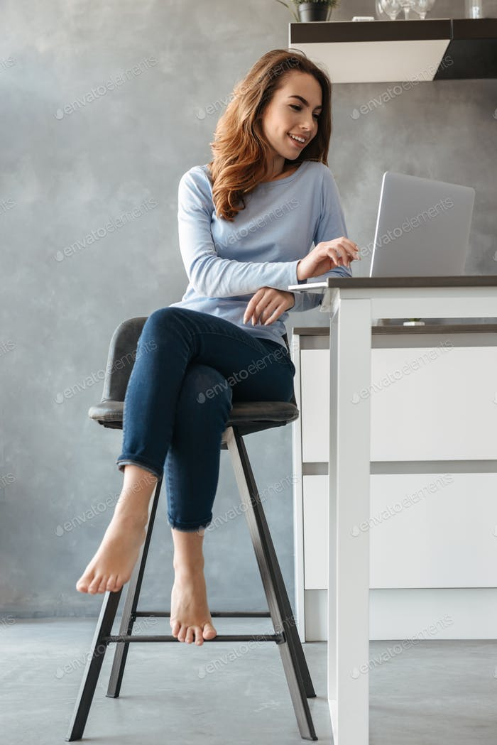 Portrait of a smiling young woman using laptop computer