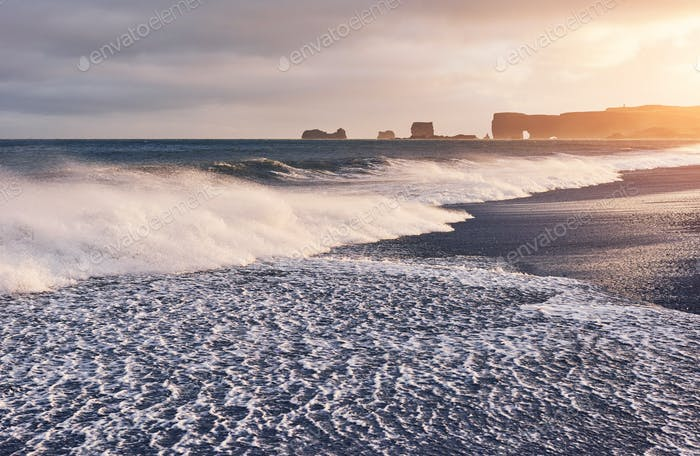 The waves hitting the beach at Black Sand Beach or Reynisfjara in Iceland