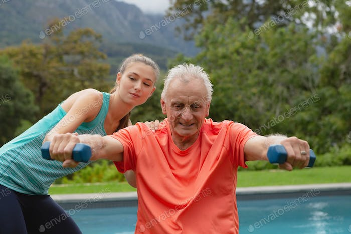 Caucasian female trainer assisting active senior man to exercise with dumbbells in the backyard