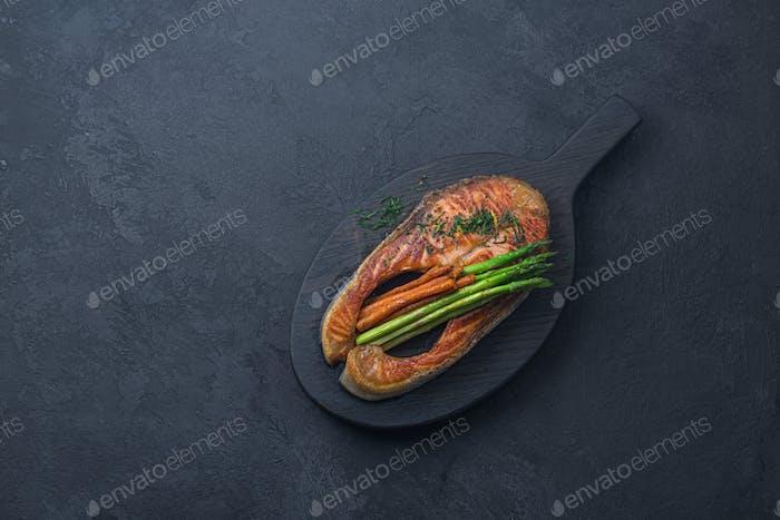 Gebratenes Lachssteak auf schwarzem Holzbrett, dunkler Fotokopierraum