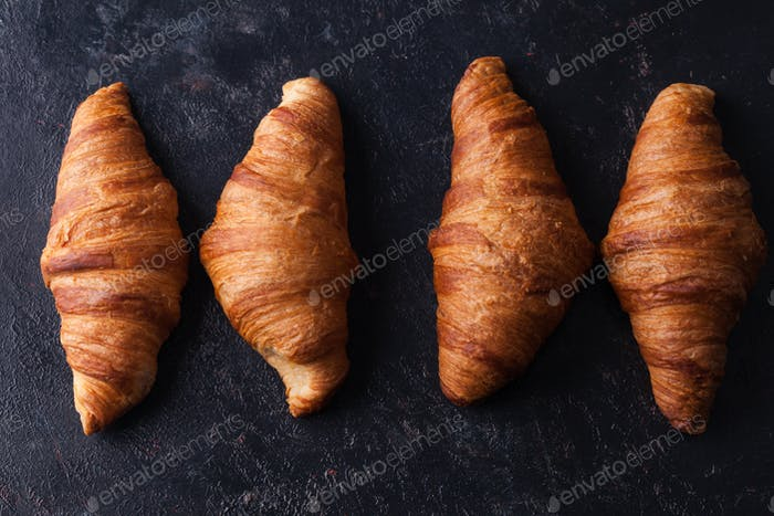 Fresh baked traditional croissants on dark wooden table
