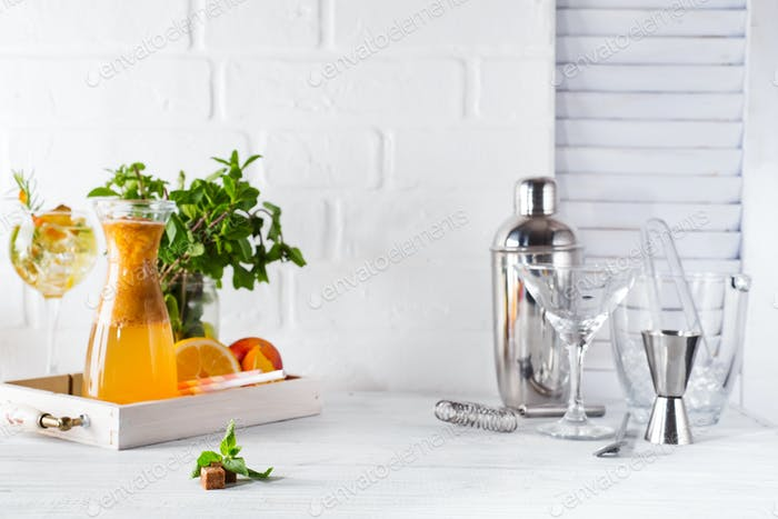 lemonade in the decanter on a wooden tray and Cocktail shaker for preparing a summer cocktail
