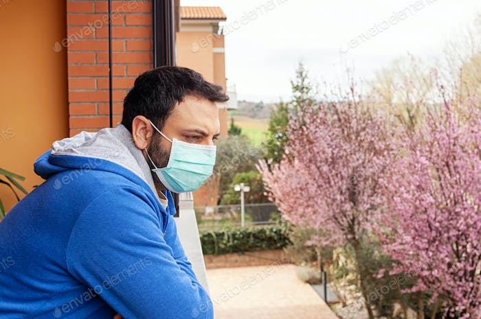 Man with mask using mobile phone during quarantine due to coronavirus