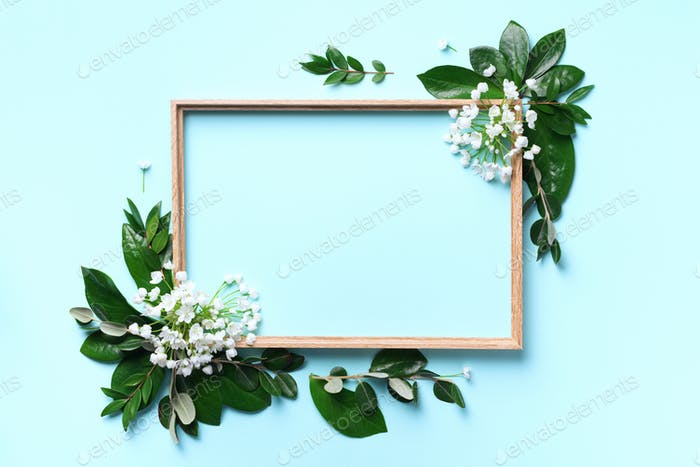 Creative layout with white flowers and copyspace over blue background. Top view, flat lay. Spring