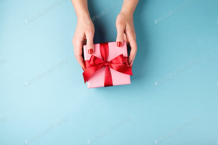 Female`s Hand Holding Pink Gift Box with Red Bow,