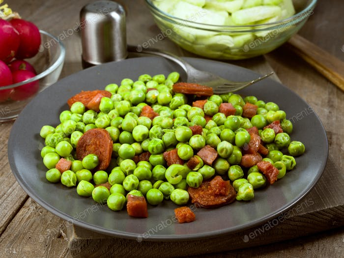 dish cooked with ham and chorizo peas in old wooden classic