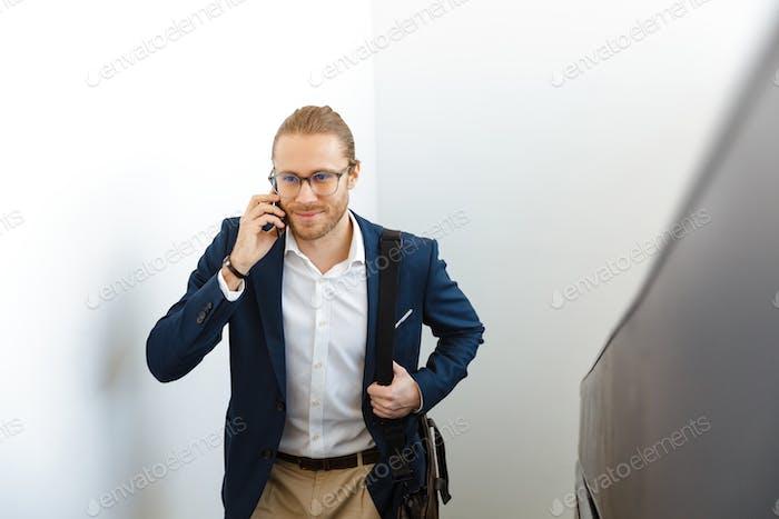 Businessman indoors walking by upstairs