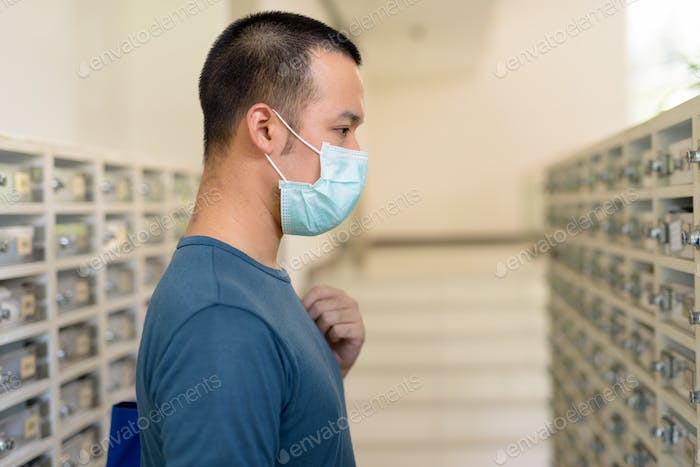 Young Asian man with mask checking the mailbox