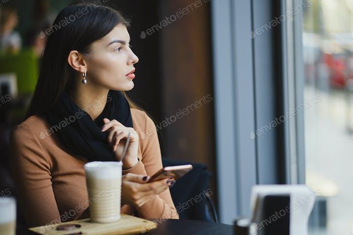 Brünette Mädchen mit Telefon während bei ein restaurant
