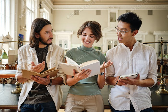 Young multinational students happily studying with book and making notes together in library