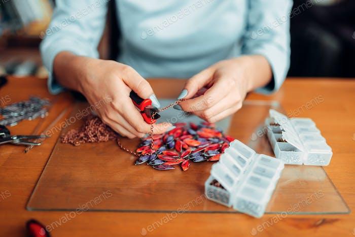 Weibliche Hände mit Zange, bijouterie machen