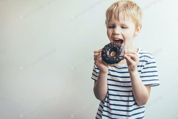 Der Teenie-Junge beißt einen Schoko-Donut. Lustiges Portrait eines Kindes.