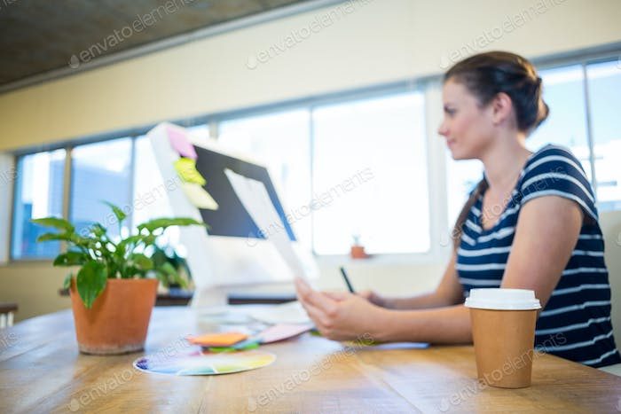 Smiling brunette working with photographs and digitizer in the office