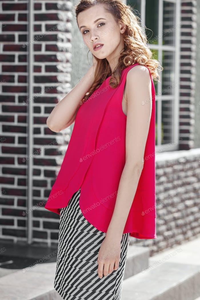 Schöne stilvolle Mädchen gekleidet in fuchsia Farbe Top und schwarz und weiß Rock Posen in der Stadt