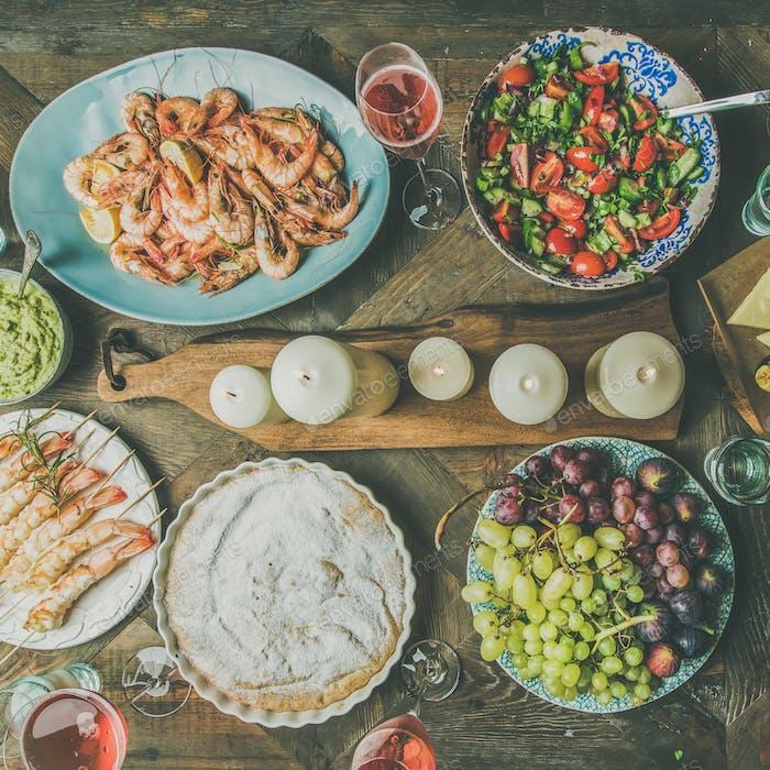 Flat-lay of salad, shrimps, olive, grape, cake, square crop