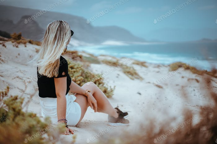 Woman sitting on white sand dune with barren vegetation admiring coastline landscape and atlantic