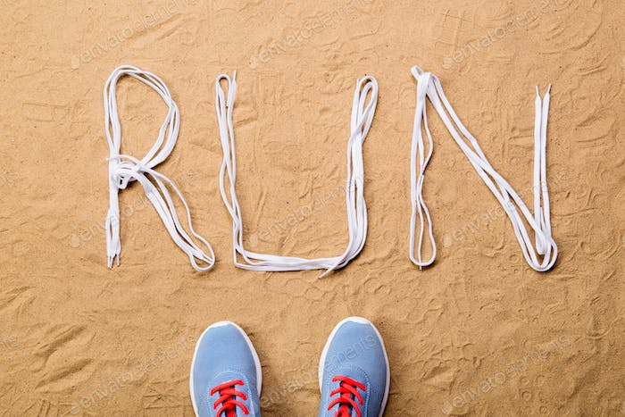 Running shoes and run sign made of shoelaces, sand