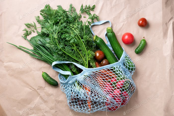Eco friendly mesh bag with organic green vegetables. Flat lay, top view. Zero waste, plastic free