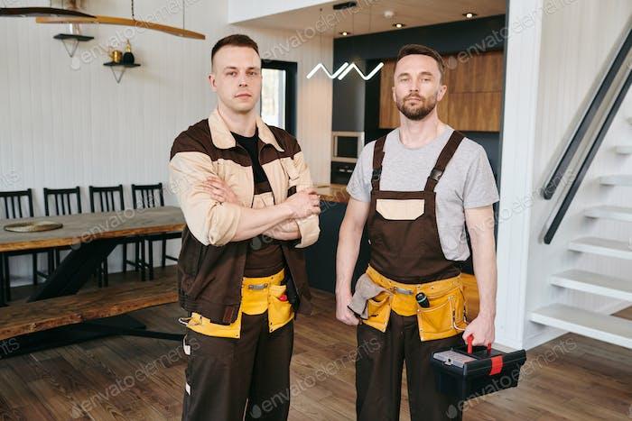 Two plumbers or repairmen in workwear