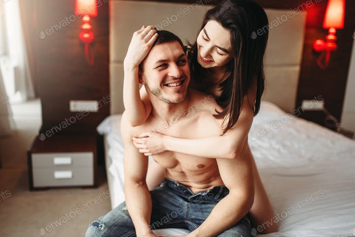 Happy love couple hugging on big white bed