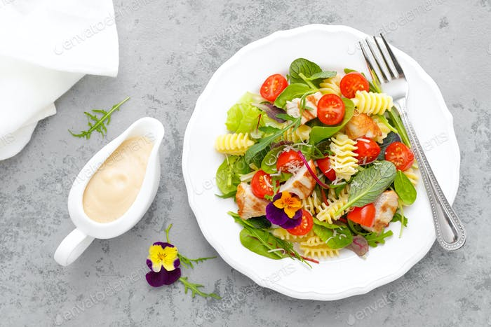 Pasta salad with grilled chicken meat, vegetables and cheese