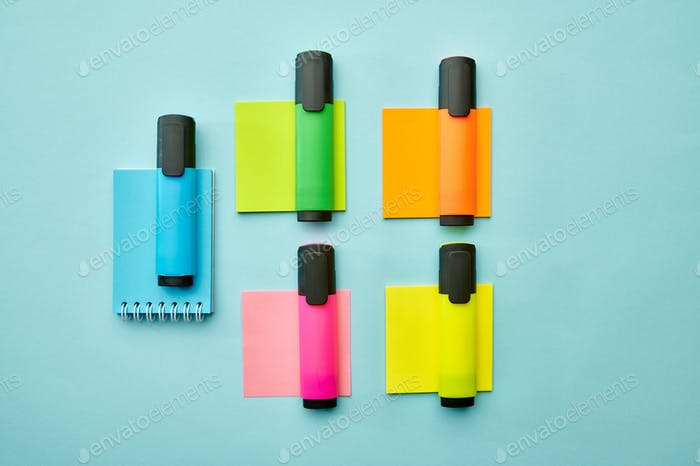 Colorful markers and notepads on blue background