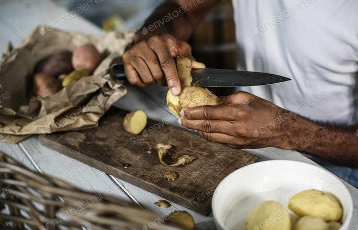 Closeup of hand with knife peeling potato skin
