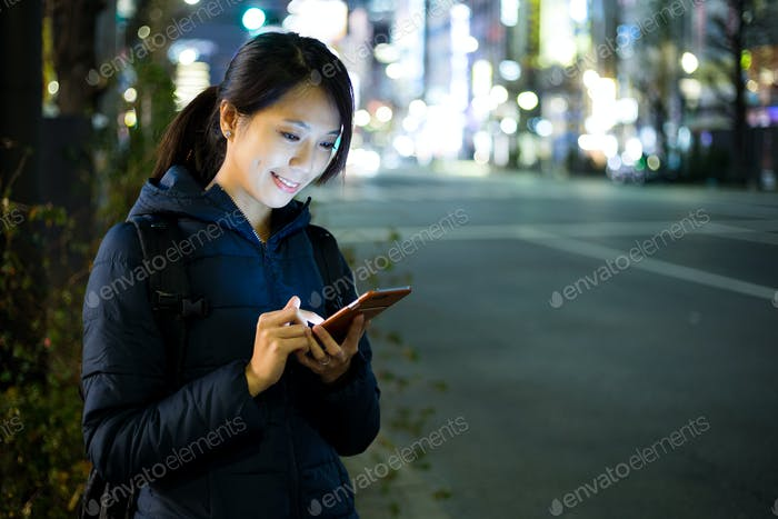 Woman use of cellphone and standing beside the road
