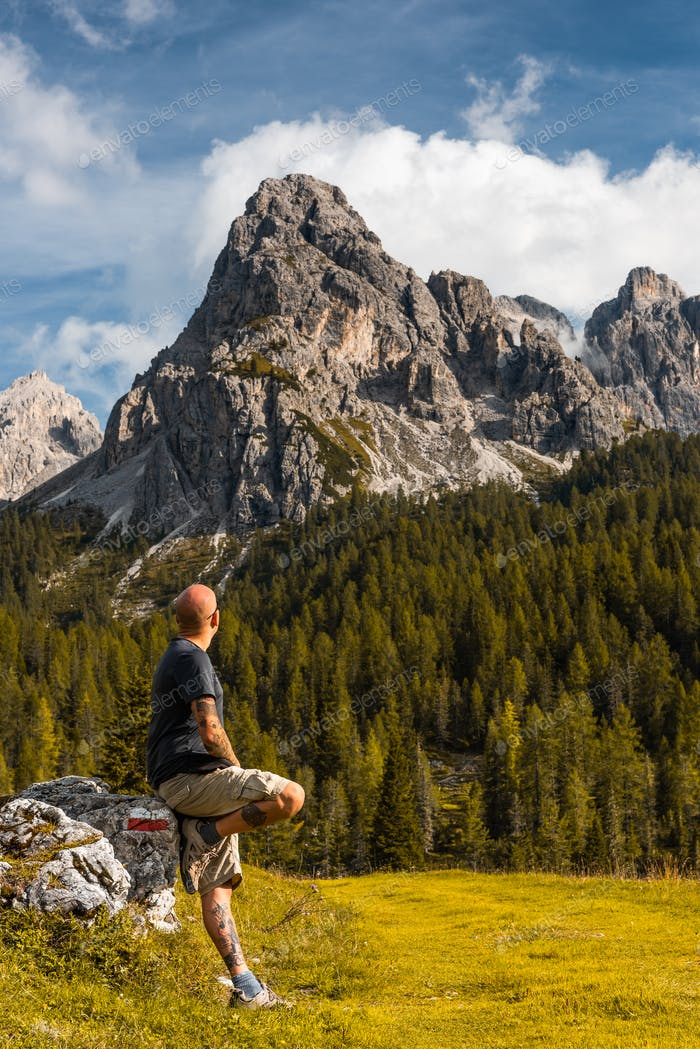 Adventure Man sSitting on Rock after Solo Hiking Dolomites Mount